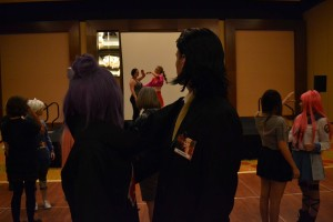 Cosplayers watch instructors as they learn to waltz for a masquerade ball.