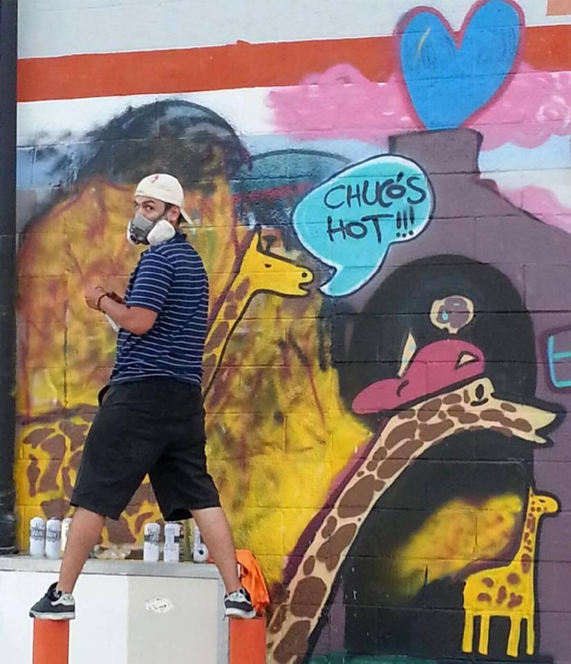 Senior psychology major Joseph Peterson spray paints a wall in Downtown El Paso.