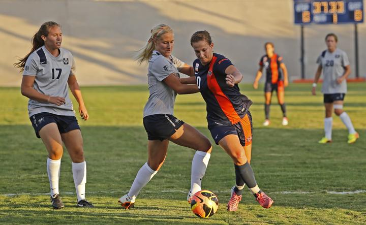 Senior midfielder Tori Martyn dribbles and attempt to elude two Utah State defenders on Aug. 30 at University Field