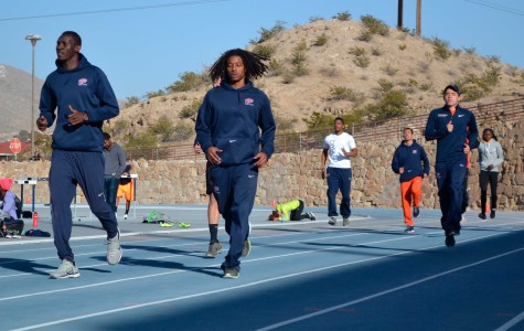 Men's 4x4 relay members Abiola Onakoya (left) and Carnell Horn (right) warmup at the Kidd Field.