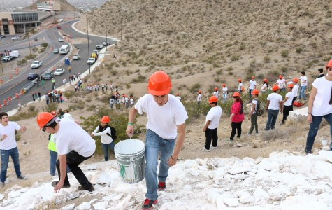 Computer science major Jade Garcia climbs up mountain to dump a bucket of paint.