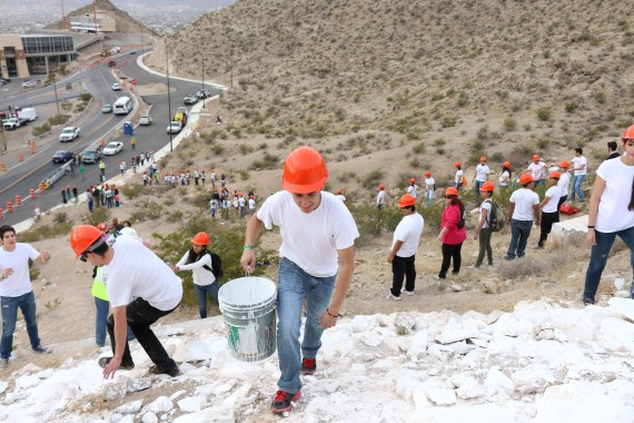 Computer+science+major+Jade+Garcia+climbs+up+mountain+to+dump+a+bucket+of+paint.+