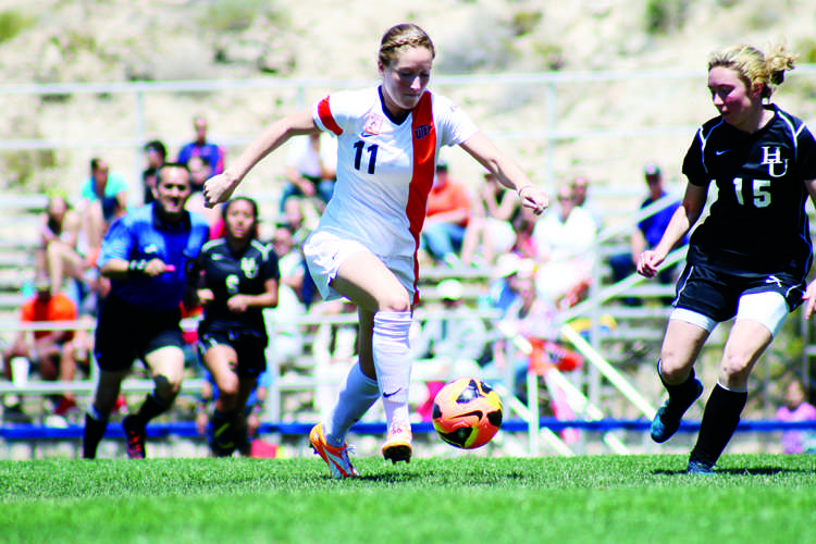 Sophomore forward Angela Cutaia eludes a New Mexico Highlands defender at University Field on April 13.