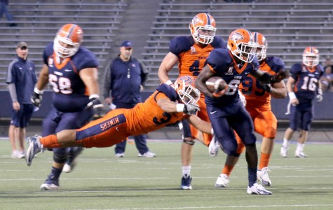 Sophomore running back Autrey Golden breaks a tackle from senior linebacker Anthony Puente during the Orange and Blue Game on April 11.