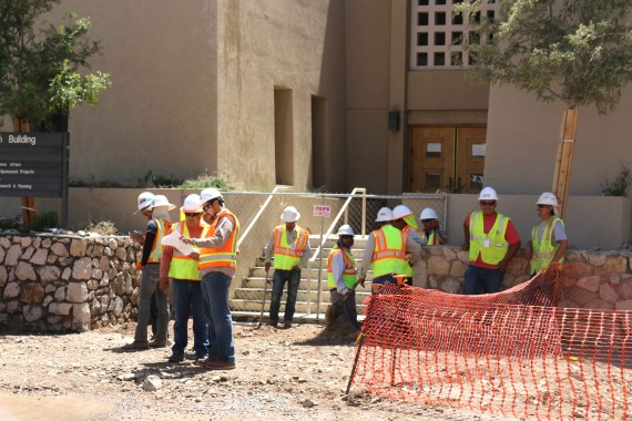 Construction workers wait for water to be turned off.