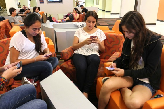 Students+check+out+the+latest+apps+on+their+smart+phones.