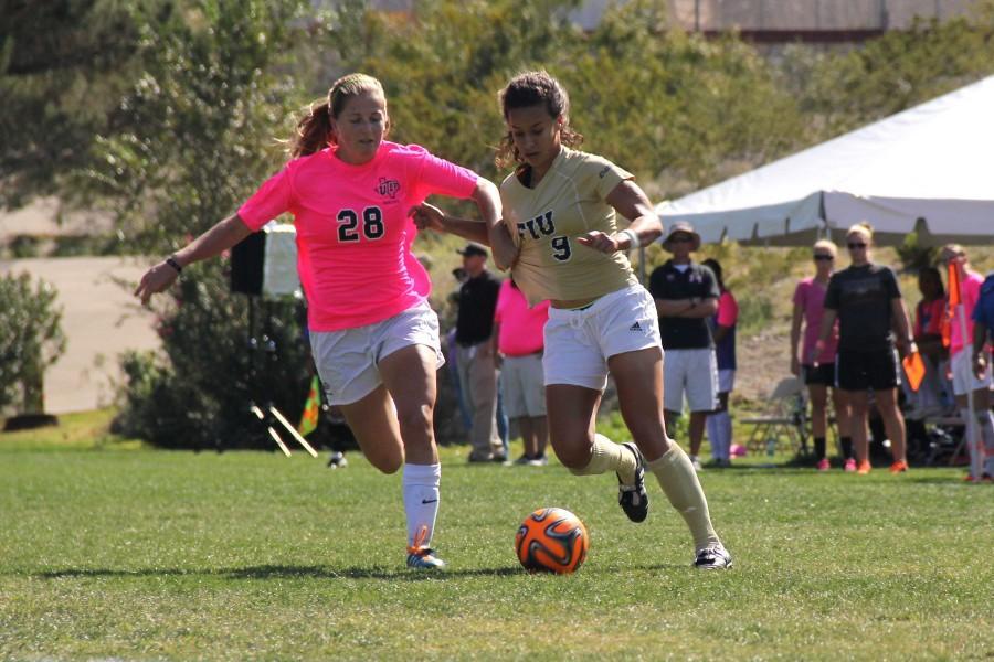 Sophomore midfielder Hannah Nicholson wins the ball against the Florida International defender this past Sunday.