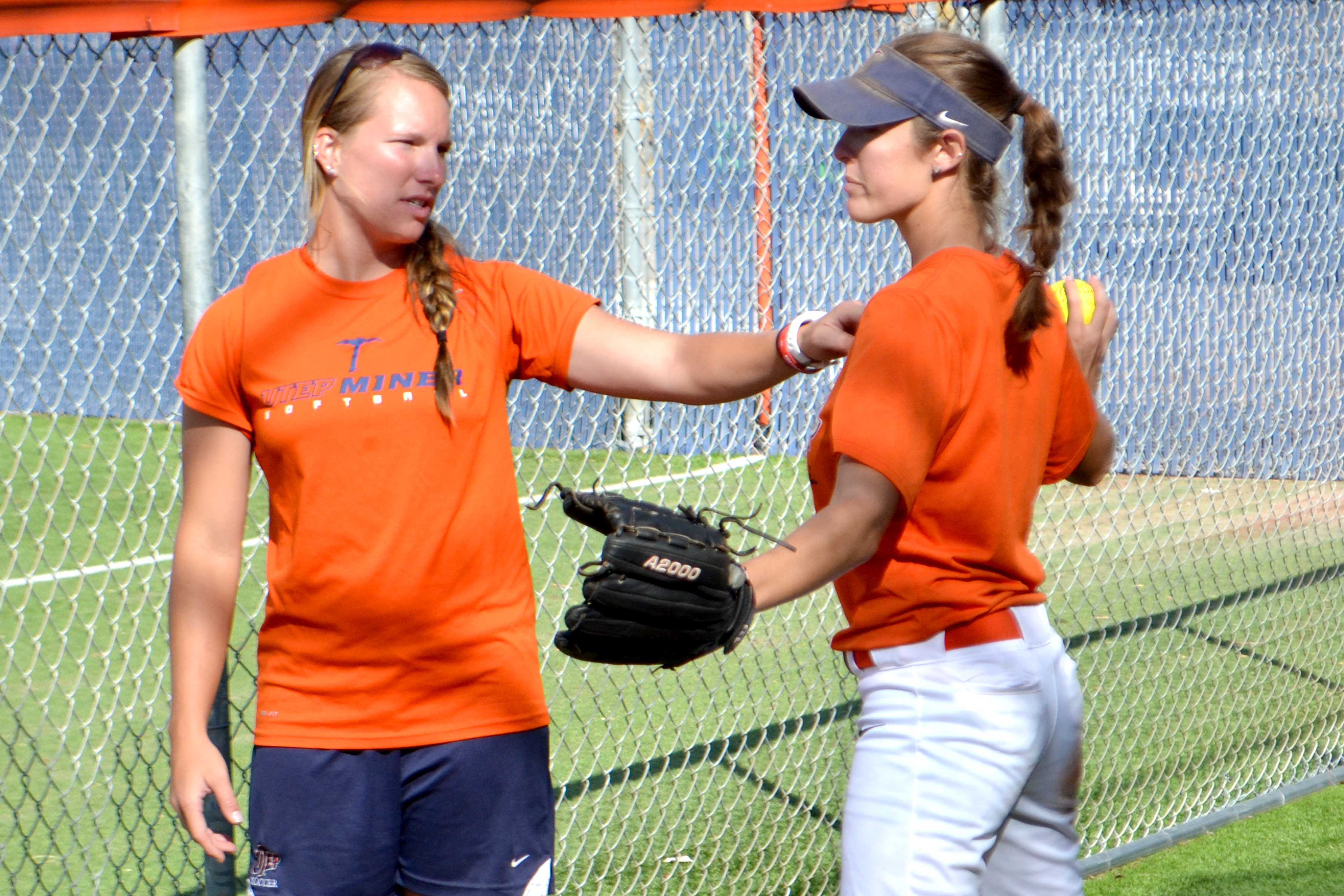 Pitching coach Sarah Plourde (left) works with junior pitcher Danielle Pearson (right) in the pitching cage.