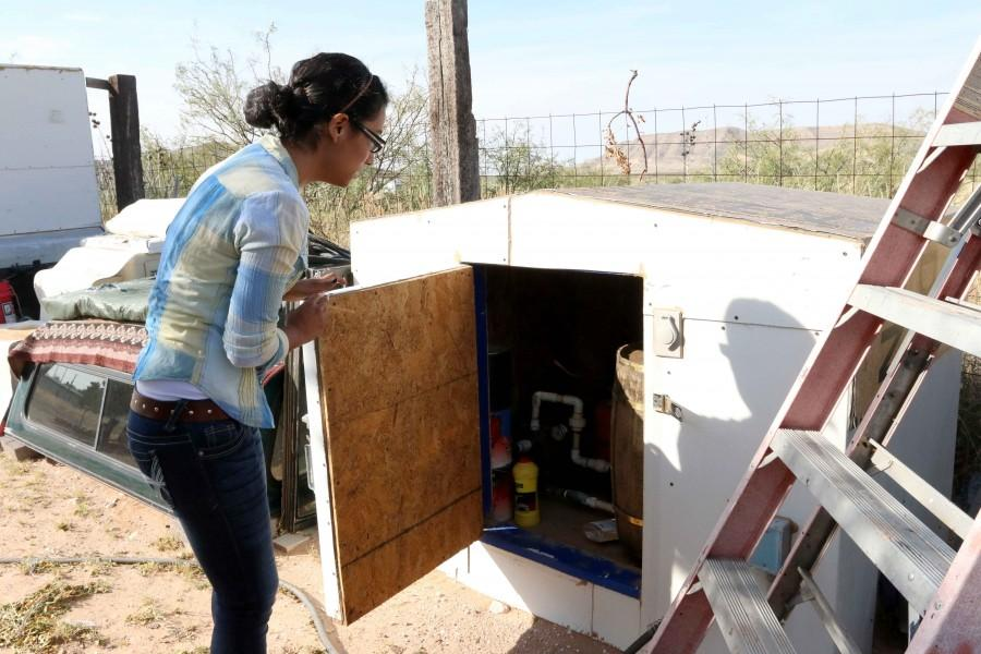 Junior multimedia journalism major Damaris Reyes demonstrates the way her family collects water for daily use.