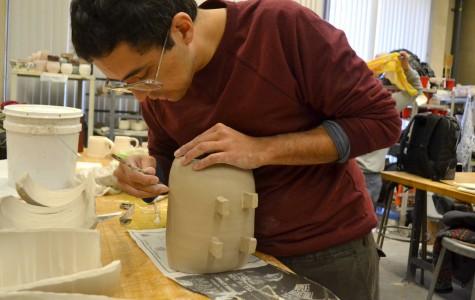 Senior studio art major Alejandro Perea works on a ceramic sushi disk.