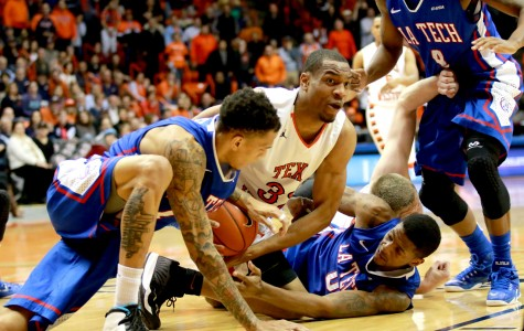 Sophomore forward Vince Hunter struggles to protect ball from Bulldog defenders.