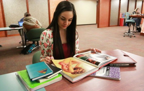 Senior multimedia journalism major Ashley Bazan reads through a fashion textbook.