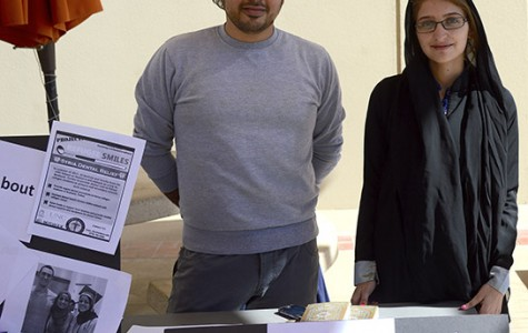 Reem Issa, right, poses behind her table, which UTEP helped to set up to promote awareness toward Muslims on campus.