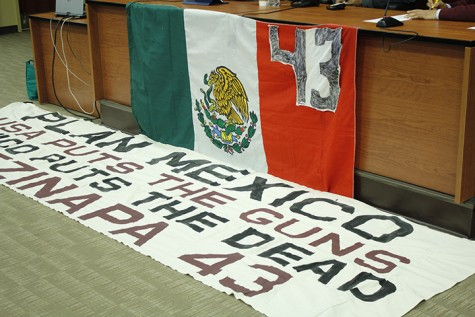 "A sign reading ""USA puts the guns, Mexico puts the dead, Ayotzinapa 43"" lies on the floor of a room at the University of the District of Columbia. It is intended to address the issue of ongoing violence in Mexico and that the U.S. it the main supplier of guns to Mexican drug cartels."