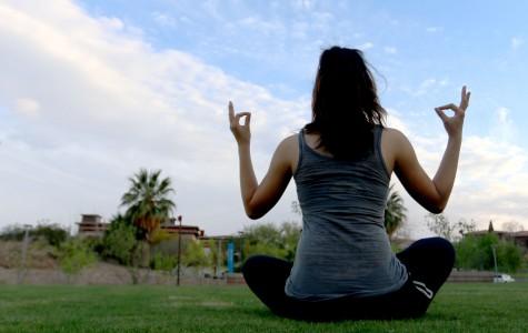A student meditates on open grass at Centennial Plaza.