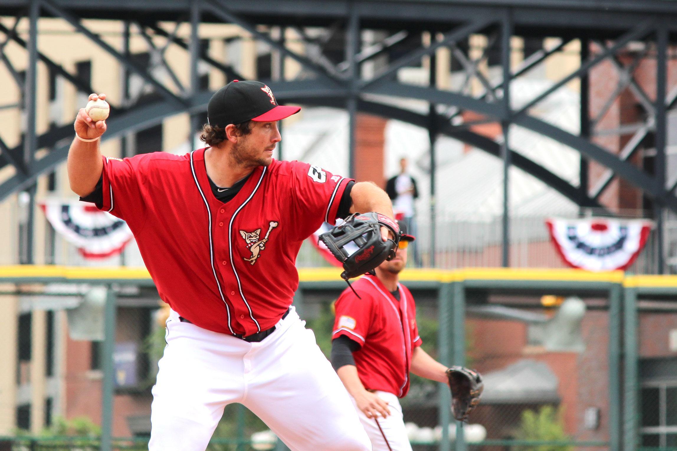Chihuahuas third baseman Brett Wallace throws the ball toward first base during the team's season opener.