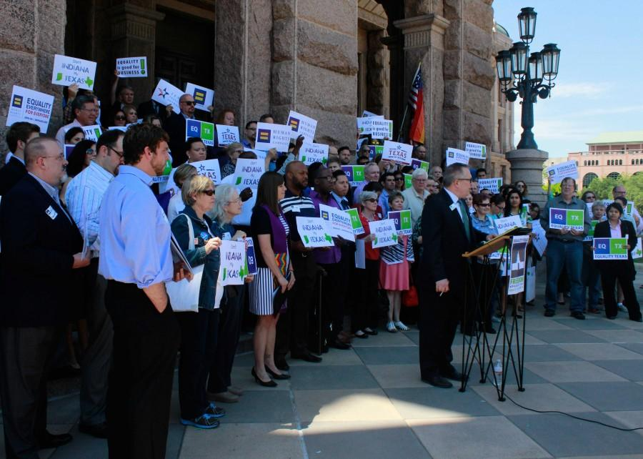 Participants stand behind Chuck Smith, executive director of Equality Texas while he speaks at the rally.