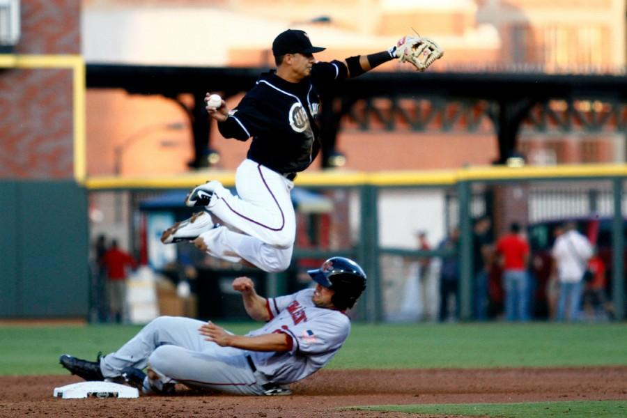 Second baseman Ramiro Pena avoids the slide while throwing towards first base.