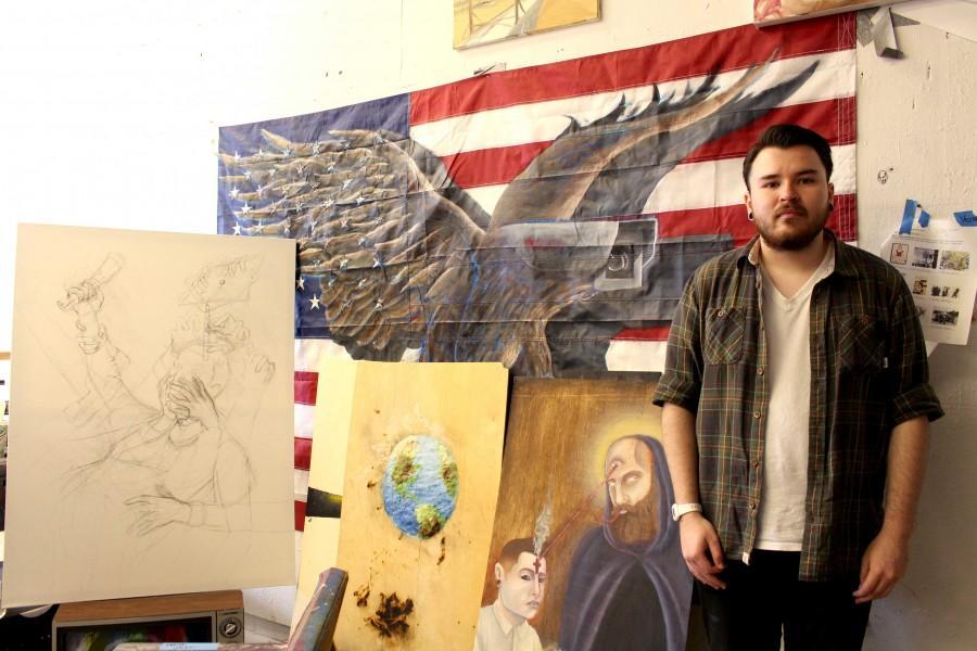 Senior+studio+art+major%2C+Deven+Mc+Coy%2C+stands+infront+of+his+art+work+at+the+Fox+Fine+Arts+Center.+
