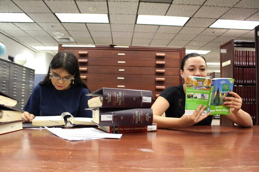 Gloria Almaguer, senior  education major, studies while Bianca Martinez, junior media advertising major, looks over a travel book at the library.