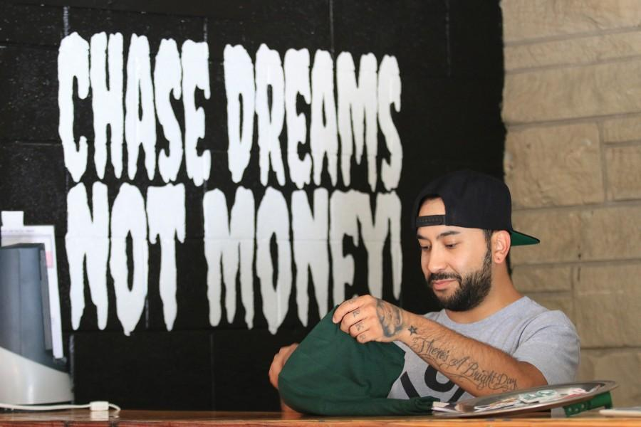 The+Dream+Chasers+Club+owner+and+founder%2C+JAM%21+folds+shirt+at+the+stores+location.