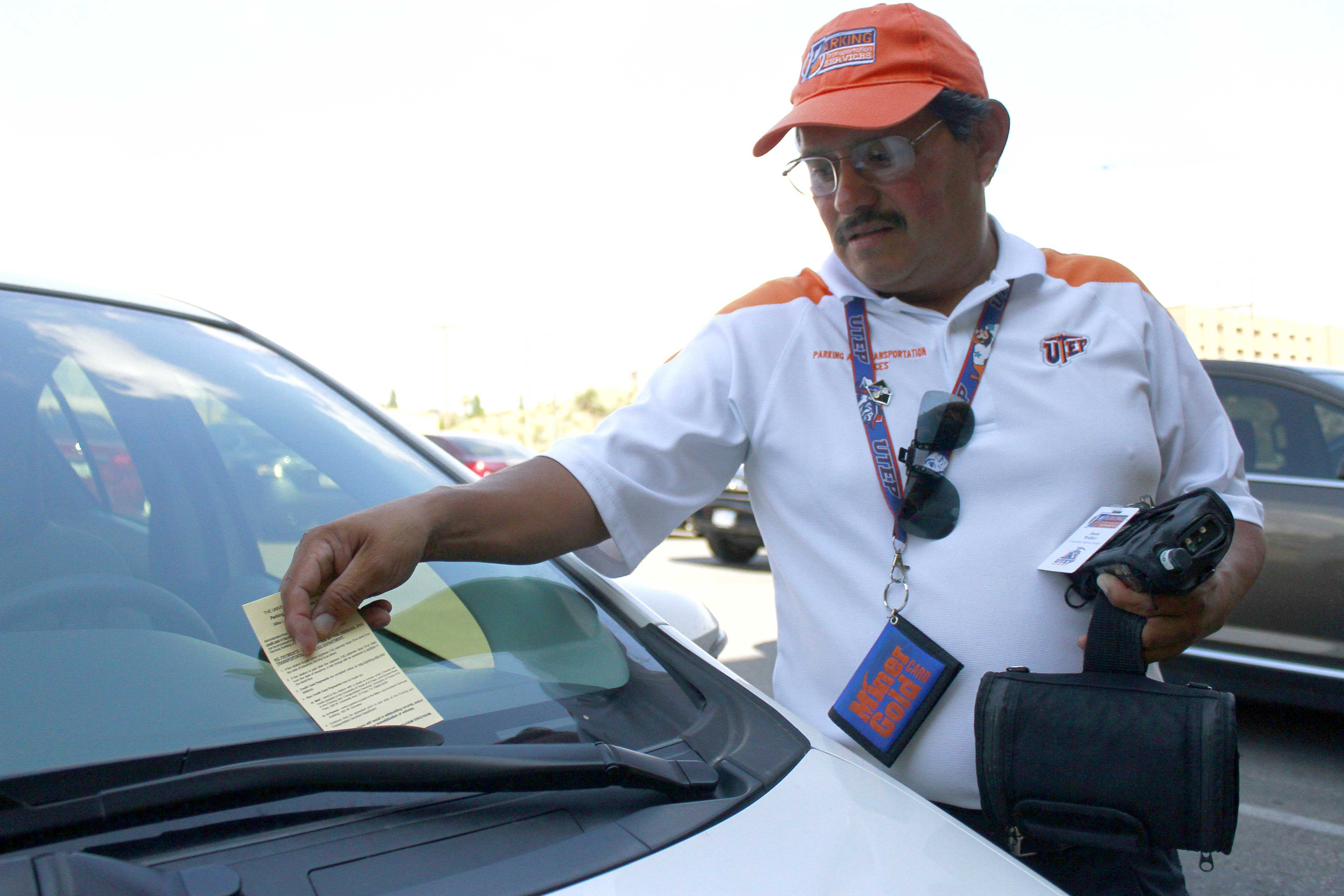 A UTEP Parking and Transportation Services employee places a citation on an illegally parked vehicle.