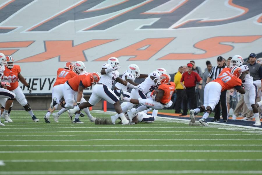 A UTEP Miner is tackled by FAU players.