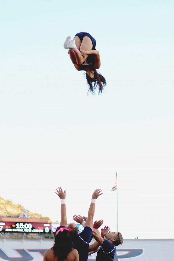 A Miner cheerleader performs a somersault.