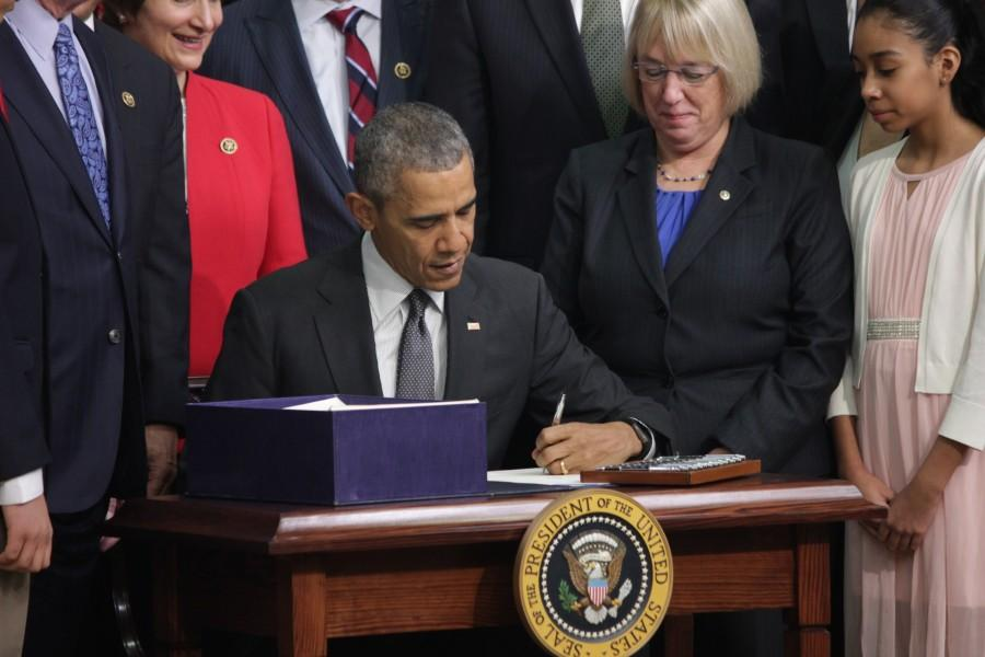 President Obama signs the Every Student Succeeds bill into law Thursday. Sen Patty Murray, D-Wash., and Sofia Rios, a eight-grade student at Kenmore Middle School in Arlington, Va., watch.