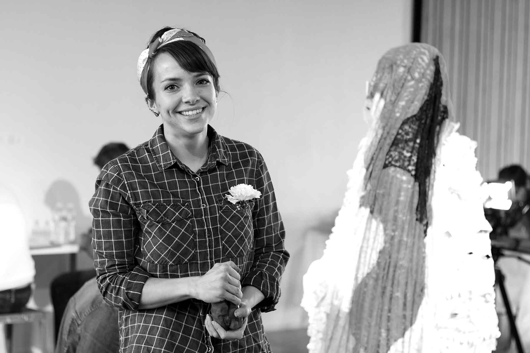 """Senior studio art major Heather Mawson molds clay as part of her piece """"Old, New, Borrowed, Blue"""" at the Glass Gallery."""