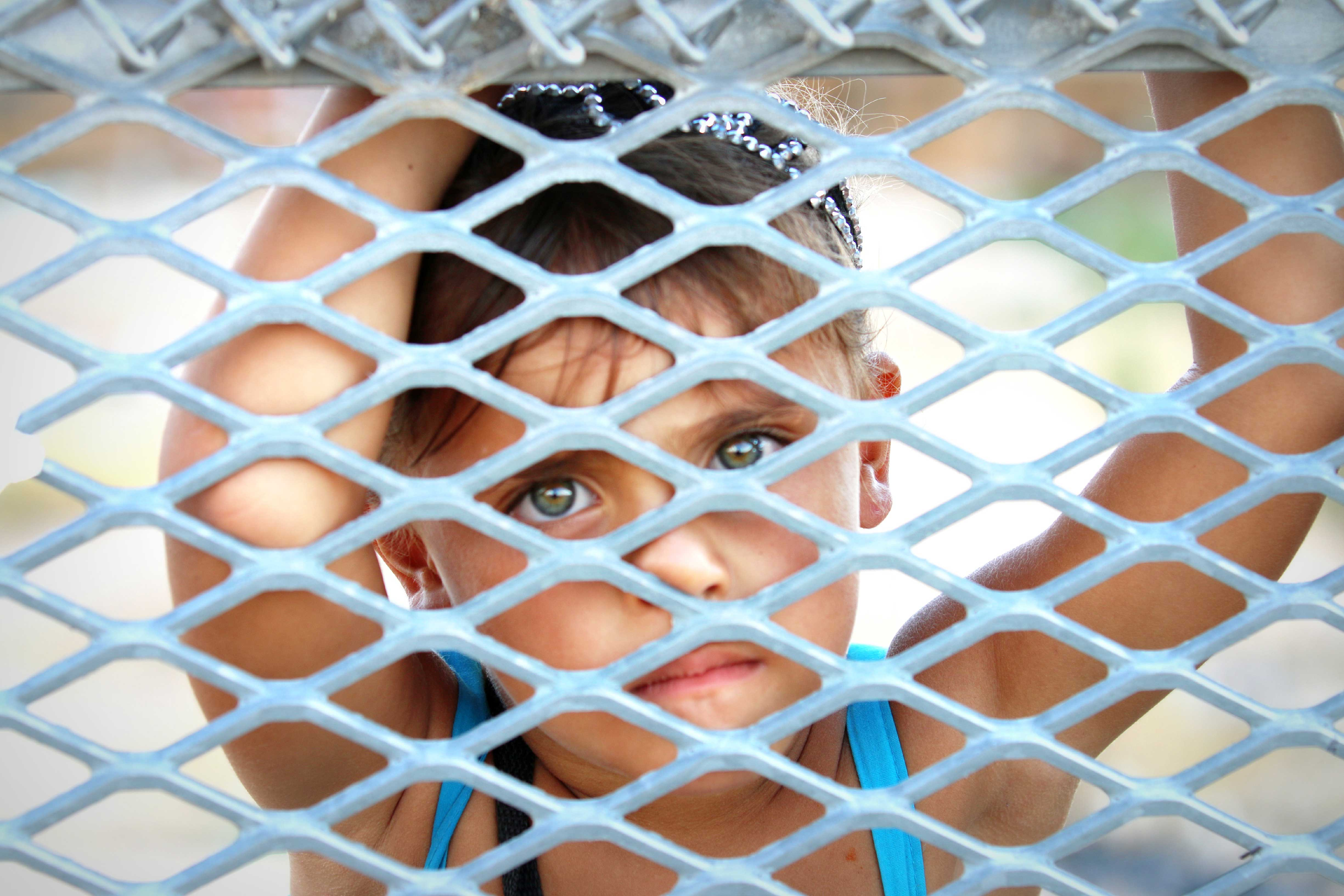 A young girl peers across the border fence into Sunland Park, New Mexico, from Ciudad Juárez, Mexico.