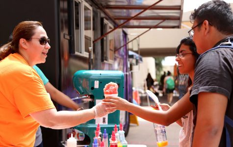 Alumni education major Diana Guerra hands out snow cones as part of the Off the Grill Food truck.