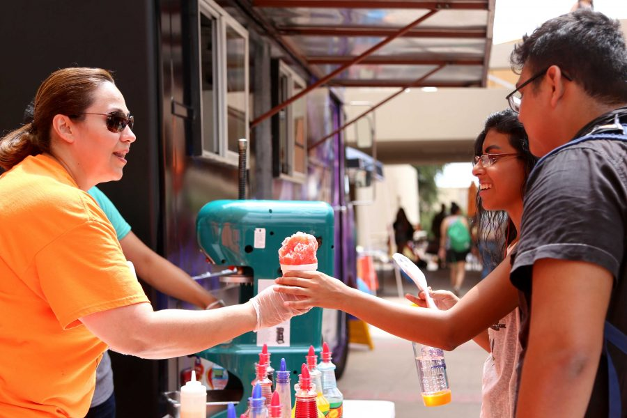 Alumni+education+major+Diana+Guerra+hands+out+snow+cones+as+part+of+the+Off+the+Grill+Food+truck.+