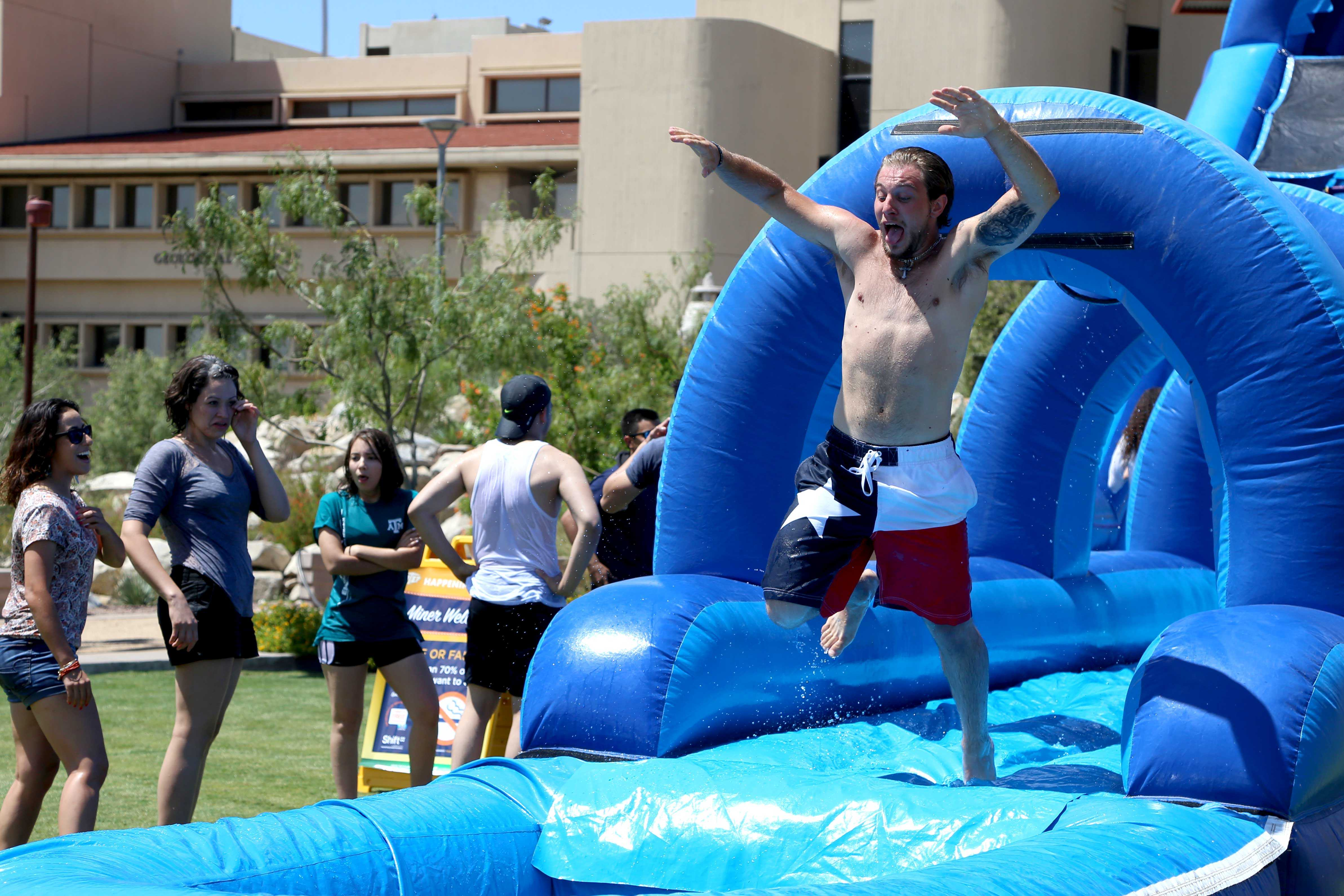 Sophomore kinesiology major Lukas Znosko makes a jump from the water slide into the little pool on the third day of school at the Centennial PLaza.