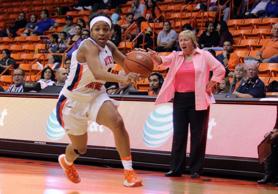 Lulu McKinney dashes the court, while Coach Keitha Adams instructs in the background