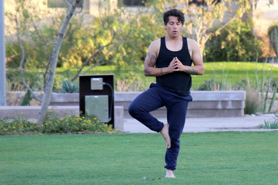 A student practices yoga in Centennial Plaza.