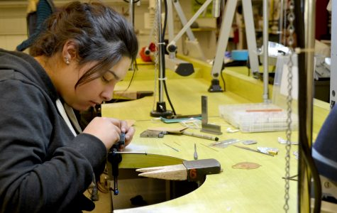 Studio major student works on creating metal jewelry.