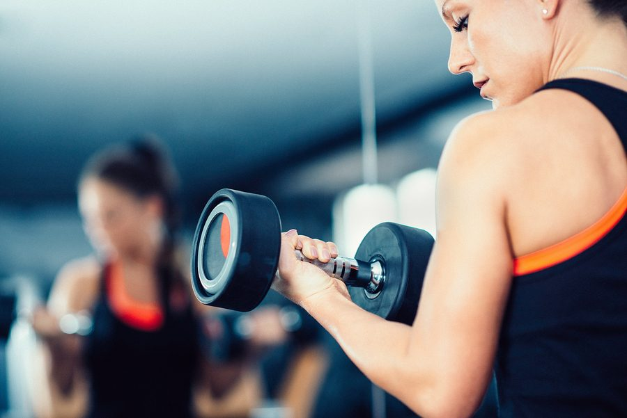 Gym Exercising - Female athlete in gym working with weights in front of mirror ** Note: Visible grain at 100%, best at smaller sizes