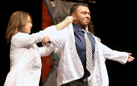 Director of experiential education clinical professor Jacquelyn P. Navarrete and chair of pharmacy practice and clinical sciences clinical professor Amanda M. Loya help students put on coats during the presentation of white coats.