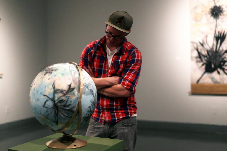 Department+studio+technician+Derek+Caulfield+observes+a+globe+from+the+%22Simplified+World%22+drawing+series.