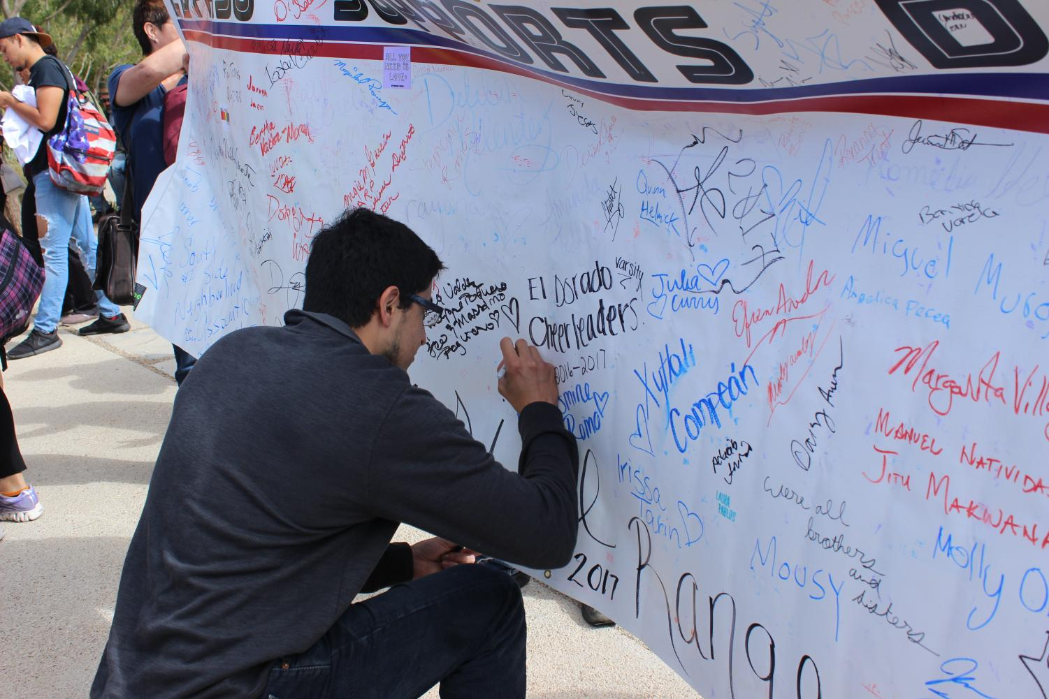 A+student+signs+his+signature+to+show+support+for+the+Dreamers.+