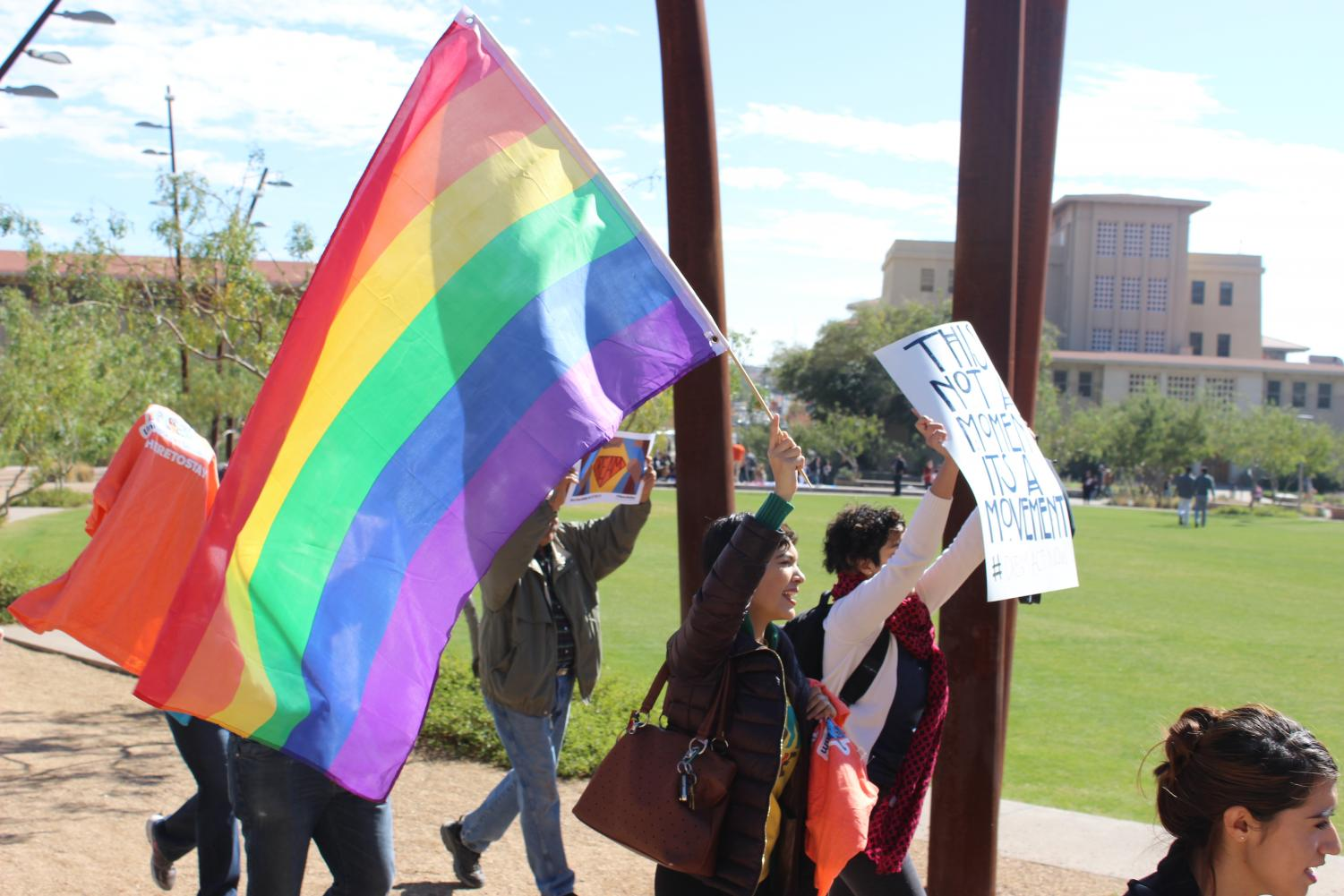 Marching around Centennial Plaza, a student holds a LGBTQ flag.