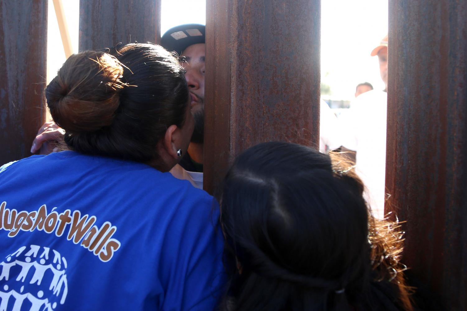 The+families+tried+to+embrace+each+other+as+best+as+they+could+across+the+fence.