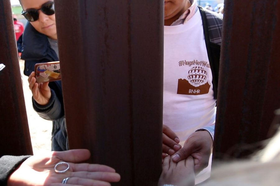 Rogelio Dominguez Parra holds Miriams Orozco Gonzalez hand minutes before getting married across the fence that divides Mexico and the U.S. on Sunday, Dec. 10, 2017.