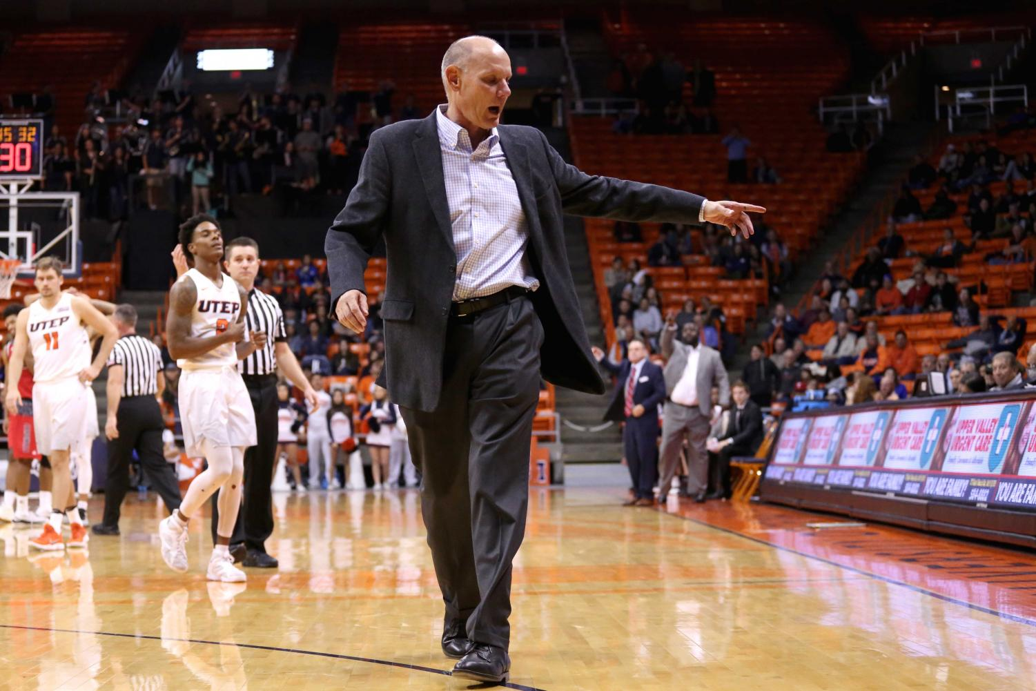 Interim head coach Phil Johnson exits the court as he is thrown out of the game.