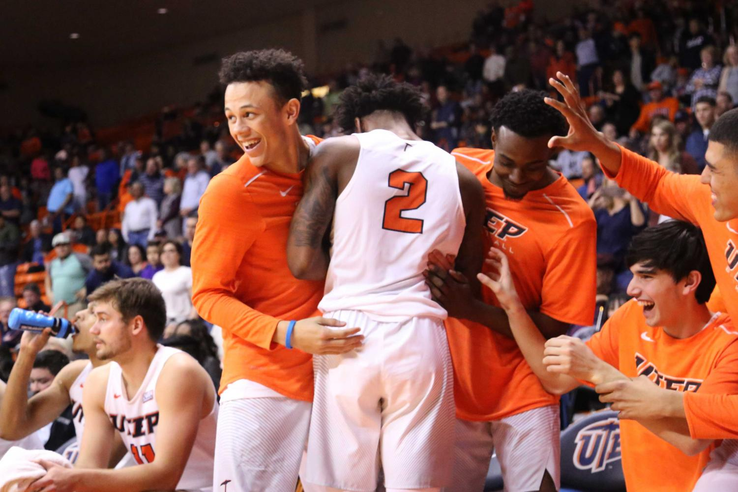 Senior guard Omega Harris hugs his teammates, after receiving a standing ovation from the home crowd.