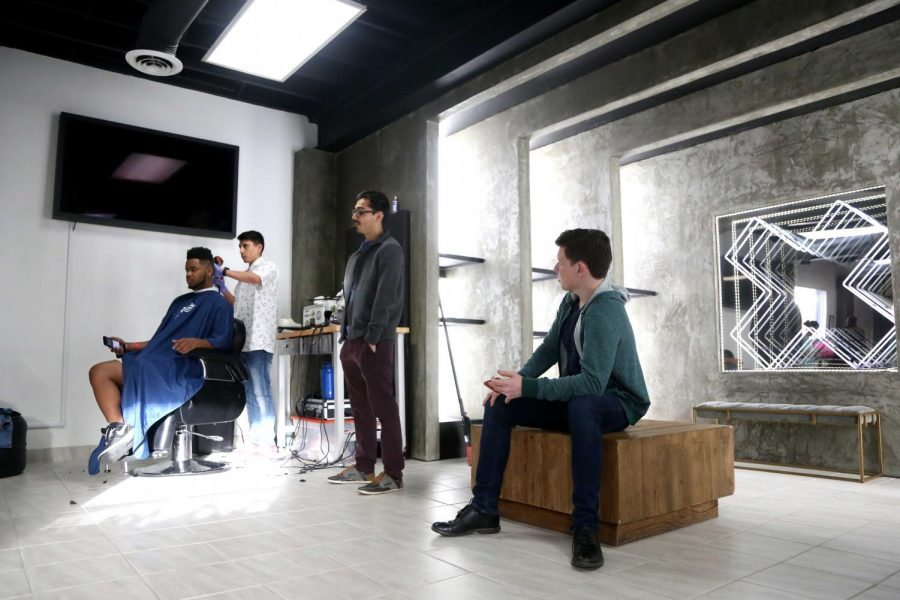 Attendees line up to get a hair cut at the Outpost Pop Up Pit Stop on Thursday, March 15.