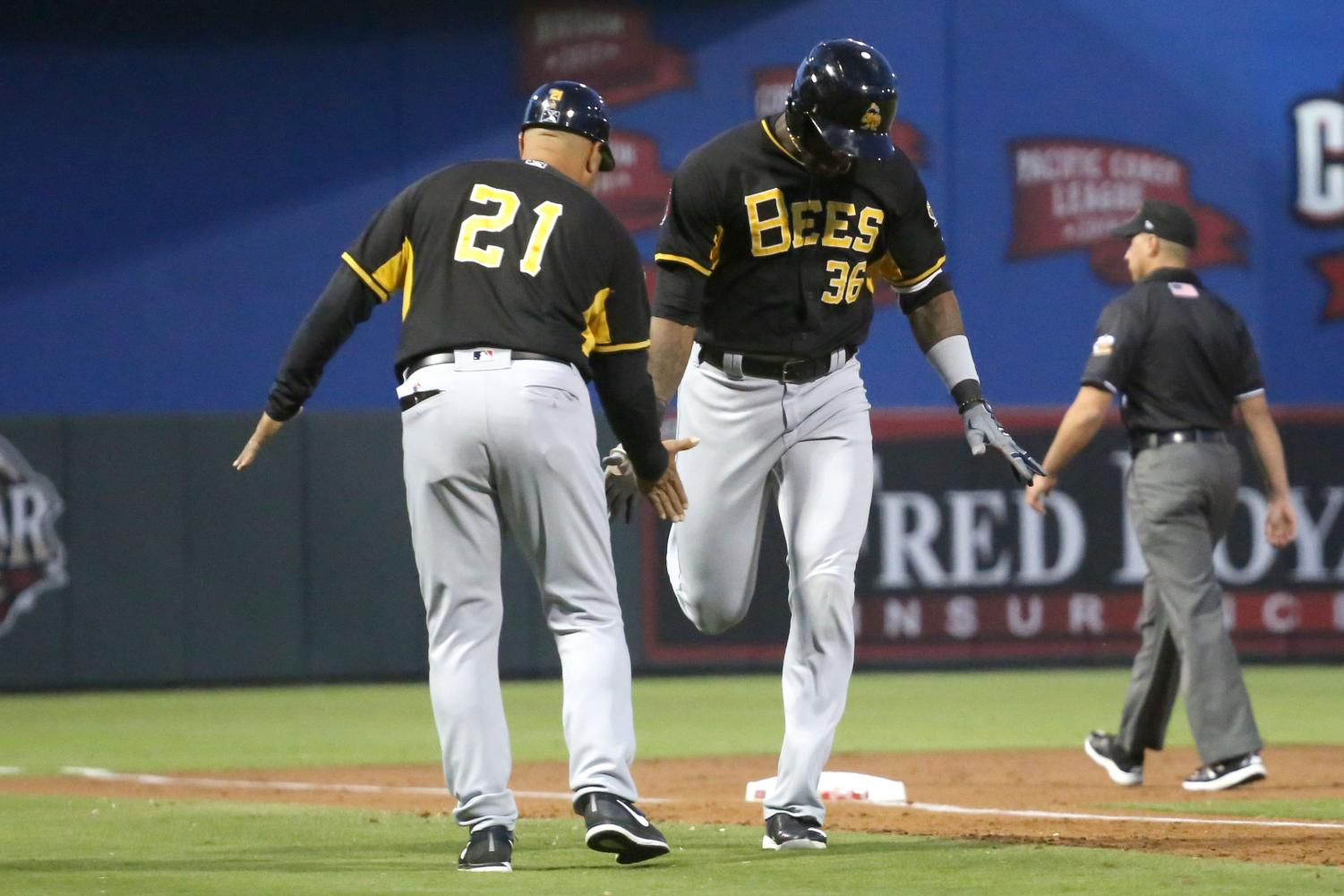 Right fielder Jabari Blash high fives manager Keith Johnson on his way to home base after hitting a home-run on the Chihuahuas opening night on Tuesday April 10 at Southwest University Park.