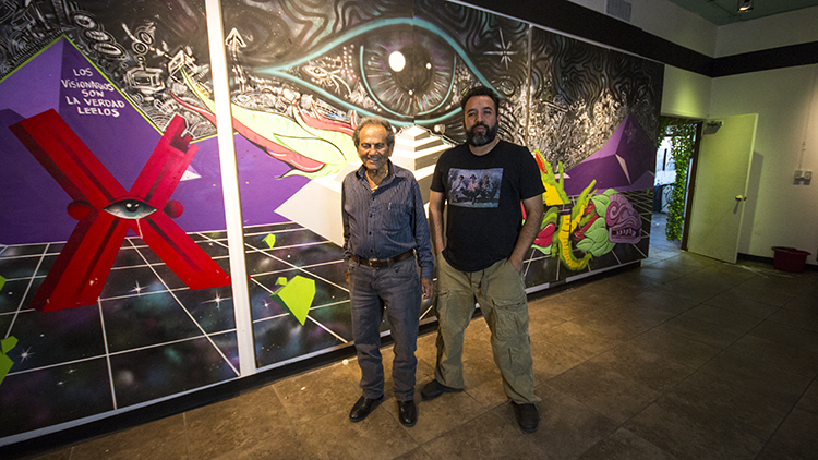 Left) Don Shapiro and Valentin Sandoval stand in front of a Los Visionaries mural at Power at the Pass. The two have partnered to start Power at the Pass, a center for artists to cultivate ideas and work on multimedia projects.