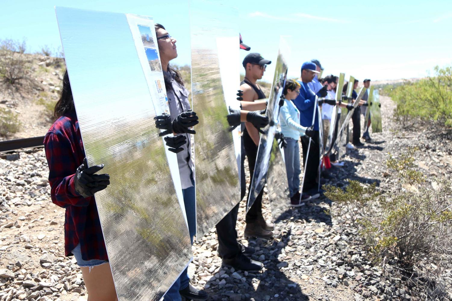 (Left) Volunteers from the El Paso and Las Cruces region hold Mylar mirror panels at Ardovino's Desert Crossing on Saturday, April 31. (Right) Artist Steven Randall instructs the volunteers on where to stand to create the mirage.